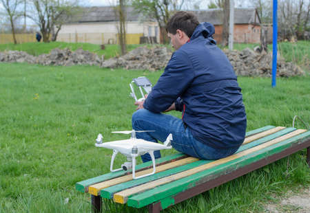 A man with a remote control quadroopter in his hands is sitting on a bench. White quadroopter prepare for flight