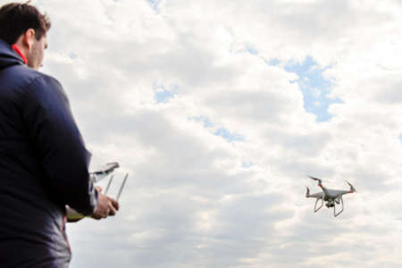 mounted: A man with a quadrocopter in his hands. White kvadrokopter prepare for flight. Stock Photo