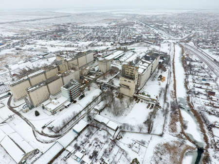 warehouse building: Sprinkled with snow grain elevator. Winter view of the old Soviet elevator. Winter view from the birds eye view of the village. The streets are covered with snow. Stock Photo