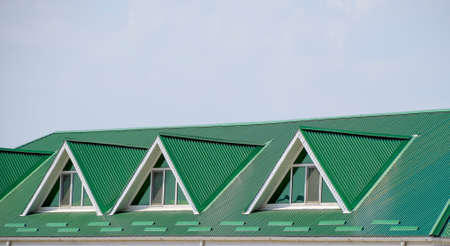 gable home renovation: The house with plastic windows and a green roof of corrugated sheet. Roofing of metal profile wavy shape on the house with plastic windows. Green roof of corrugated metal profile and plastic windows. Stock Photo
