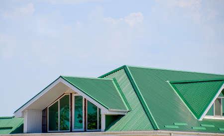 プラスチック製の窓と波板の緑の屋根の家。プラスチック製の窓が付いている家の波状形状金属の屋根ふき。段ボールの金属のプロファイルとプラ