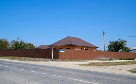 A house with a metal corrugated roof and a gauve fence made from a brown metal profile.