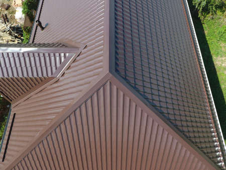 gable home renovation: The roof of corrugated sheet. Roofing of metal profile wavy shape. A view from above on the roof of the house.