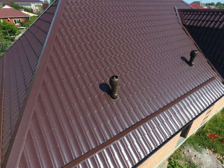 gable home renovation: The roof of corrugated sheet. Roofing of metal profile wavy shape. Air ducts on metal roof. Stock Photo