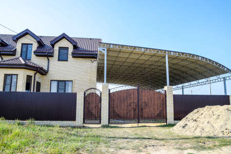 Brick house with a fence and gates. A large awning with a steel frame. View of a new built-up fence and a house made of bricks and corrugated metal