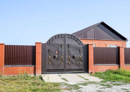spillway: Brick house with a fence and gates. View of a new built-up fence and a house made of bricks and corrugated metal