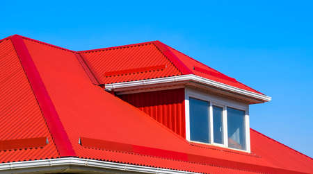 House with plastic windows and a red roof of corrugated sheet. Roofing of metal profile wavy shape on the house with plastic windows.