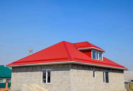Red corrugated roof. House of cinder block. The house with plastic windows and a roof of corrugated sheet.