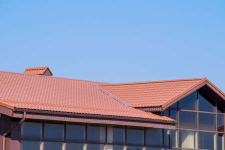 A building with a red-brown roof. Modern materials of finish and roofing.