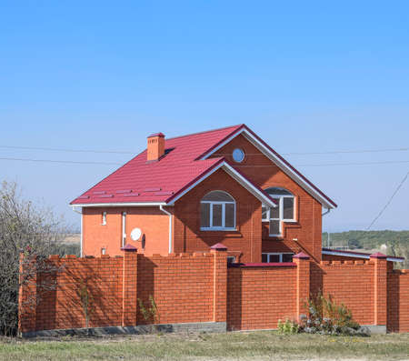 house with a red roof and red brick. Red brick fence. Roof of metal