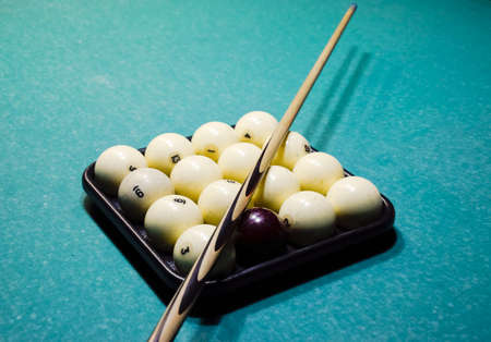 Billiards, billiard table, balls and cue. Balls in the tray and cue on the balls. Stock Photo