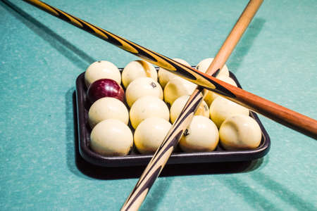 Billiards, billiard table, balls and cue. Balls in the tray and two cues on the balls.