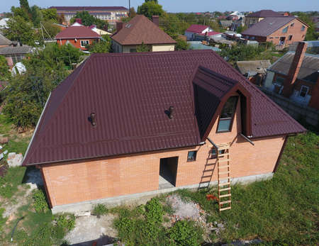 The roof of corrugated sheet. Roofing of metal profile wavy shape. House with a new metal roof.