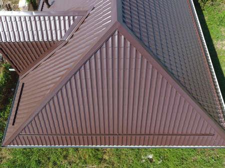 Het dak van golfplaten. Dakbedekking van golvende vorm van metaalprofiel. Een uitzicht van bovenaf op het dak van het huis.