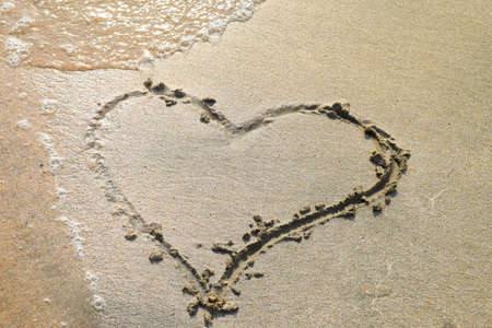 Heart drawn on the beach sand. heart symbol on the sand washed by the sea wave.