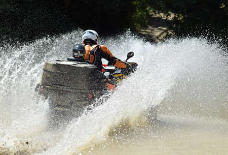 The man on the ATV crosses a stream. Tourist walks on a cross-country terrain. Stock Photo - 87996811
