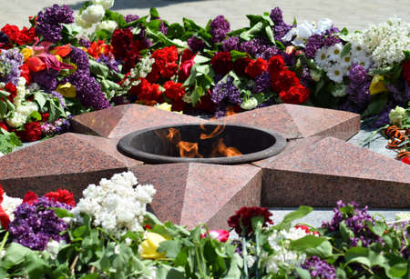 Eternal flame with flowers assigned to it. Celebration of May 9 Victory in the Great Patriotic War.
