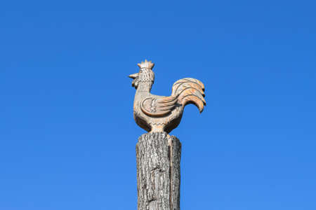animal figurines: Figurine of a rooster on a tree stump on a background of blue sky. Figures of animals made of wood. Woodcarving.