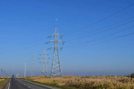 Support of electricity cables along the road. Country road. Stock Photo