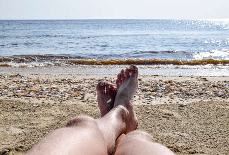 seascapes: The legs of a man on a beach background. A man lies on an amatrace on the beach and is resting. Legs in the frame