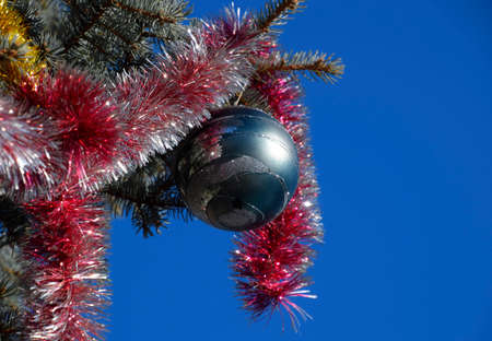 tinsel: Decorations New Year tree. Tinsel and toys, balls and other decorations on the Christmas Christmas tree standing in the open air. Stock Photo