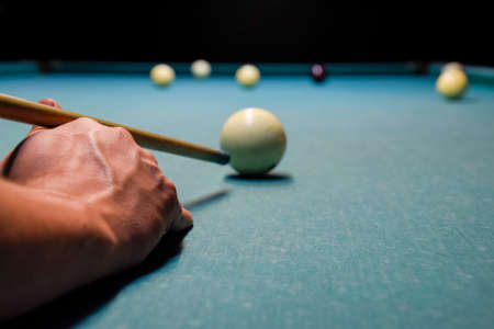 Billiards, billiard table. Targeting the cue in the ball for impact.