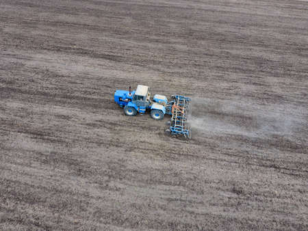 Cultivation of soil for the sowing of cereals. Tractor plows the soil on the field.