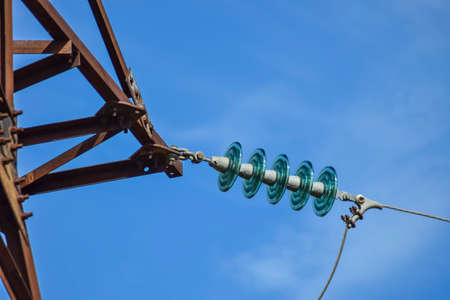 Glass prefabricated high voltage insulators on poles high-voltage power lines. Electrical industry. Stock Photo