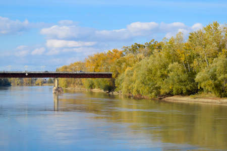 Bridge over the river. Autumn leaves on poplars along the river bank Stock Photo