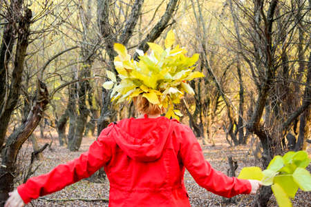 Rear view of a girl with a wreath of foliage on her head. Girl in a red jacket. Girl in a red jacket with a wreath of yellow autumn leaves. The Queen of Autumn. Miss autumn. Autumn Walk. Stock Photo