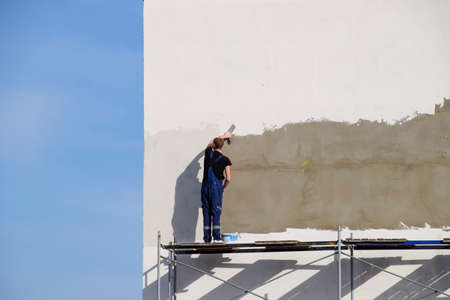 Slavyansk-na-Kubani, Russia - September 9, 2016: Plasterers Builders plastered wall in a commercial building. Work on scaffolding.