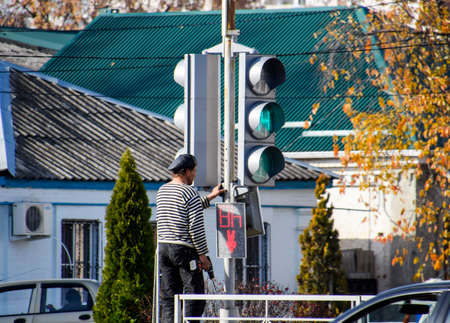 Slavyansk-na-Kubani, Russia - September 9, 2016: Electrical repairs traffic light at the intersection. Broken traffic light.