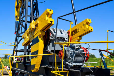 Balance weight and reducer of the pumping unit of an oil well.Equipment of oil fields. Stock Photo