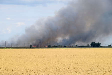 The fire is somewhere beyond the plowed field. Dark smoke from a fire
