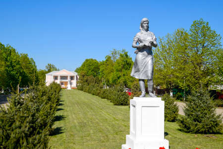 Statue of a collective farmer on a pedestal. The legacy of the Soviet era. A flower bed with tulips and young trees in the village of Oktyabrsky. Krasnodar Krai, Krasnoarmeisky District