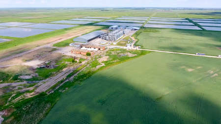 Plant for the drying and storage of grain. Rice plant in the middle of fields. Banco de Imagens