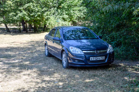Forests next to the village of Shapsugskaya, Russia - July 30, 2016: A blue Opel Astra car under a tree in the shade.