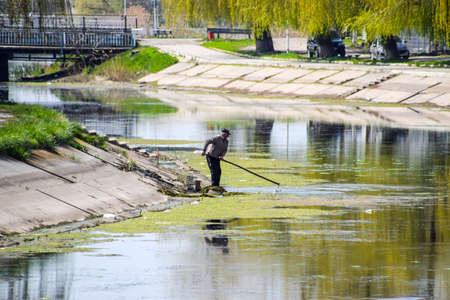 Poltavskaya, Russia - April 07, 2016: An elderly man removes garbage in a dirty city river. Editorial