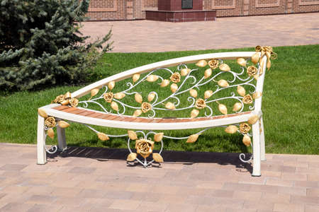 Street bench with forged patterns. Blacksmith's product. Art in a forged bench