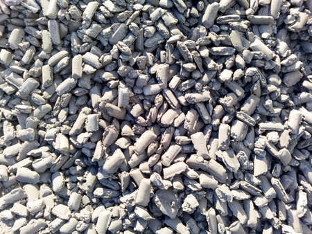 Iron in briquettes piled high in the harbor. raw steel. Stock Photo