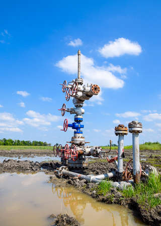 Oil well after repair in mud and puddles. Oil well wellhead equipment. Hand valve with handwheel for opening and closing the flow line