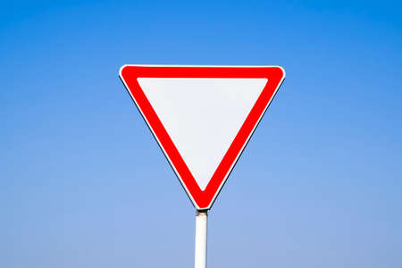 Road signs, give way. Sign on a blue background.