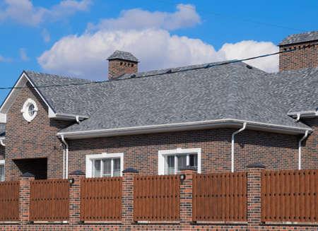 Gont asfaltowy. Dekoracyjne gonty bitumiczne na dachu domu murowanego. Ogrodzenie wykonane z blachy falistej