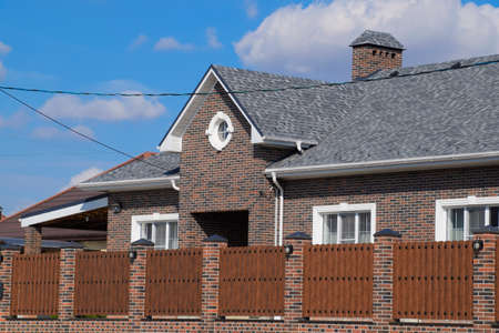 Asphalt shingle. Decorative bitumen shingles on the roof of a brick house. Fence made of corrugated metal