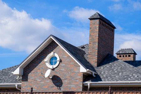 Asfalt grind. Decoratieve bitumenshingles op het dak van een bakstenen huis