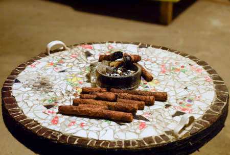 Cigar and ashtray on the table of the glued pieces of pottery. Homemade cigars from leafy tobacco leaves on a ceramic table. Ashtray and cigars. Stock Photo