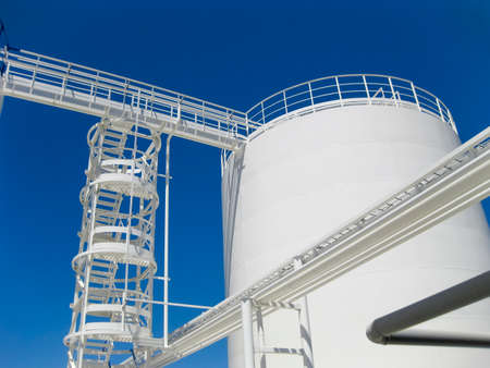 The tank with water and a ladder. Oil refinery. Equipment for primary oil refining. Banco de Imagens - 96589934