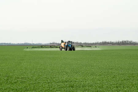 Tractor with high wheels is making fertilizer on young wheat. The use of finely dispersed spray chemicals. Tractor with a spray device for finely dispersed fertilizer. Imagens