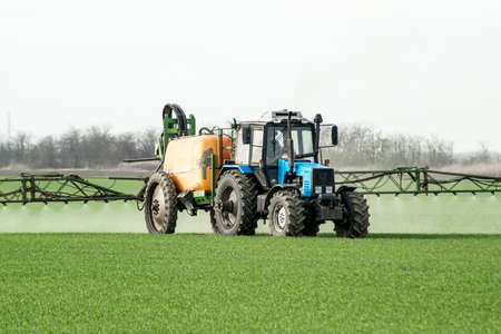 Tractor with high wheels is making fertilizer on young wheat. The use of finely dispersed spray chemicals. Tractor with a spray device for finely dispersed fertilizer. Banco de Imagens