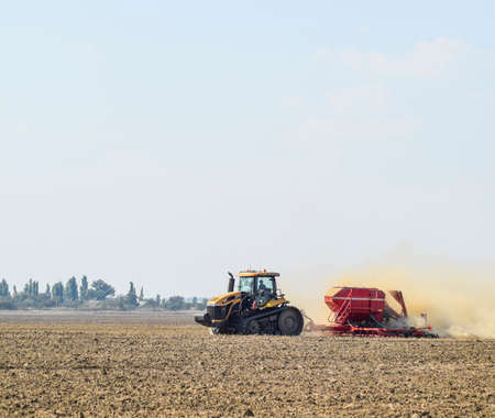 Russia, Temryuk - 19 July 2015: Tractor rides on the field and makes the fertilizer into the soil. Clouds of dust from the dry soil tractor trailer. Fertilizers after plowing the field. Redakční